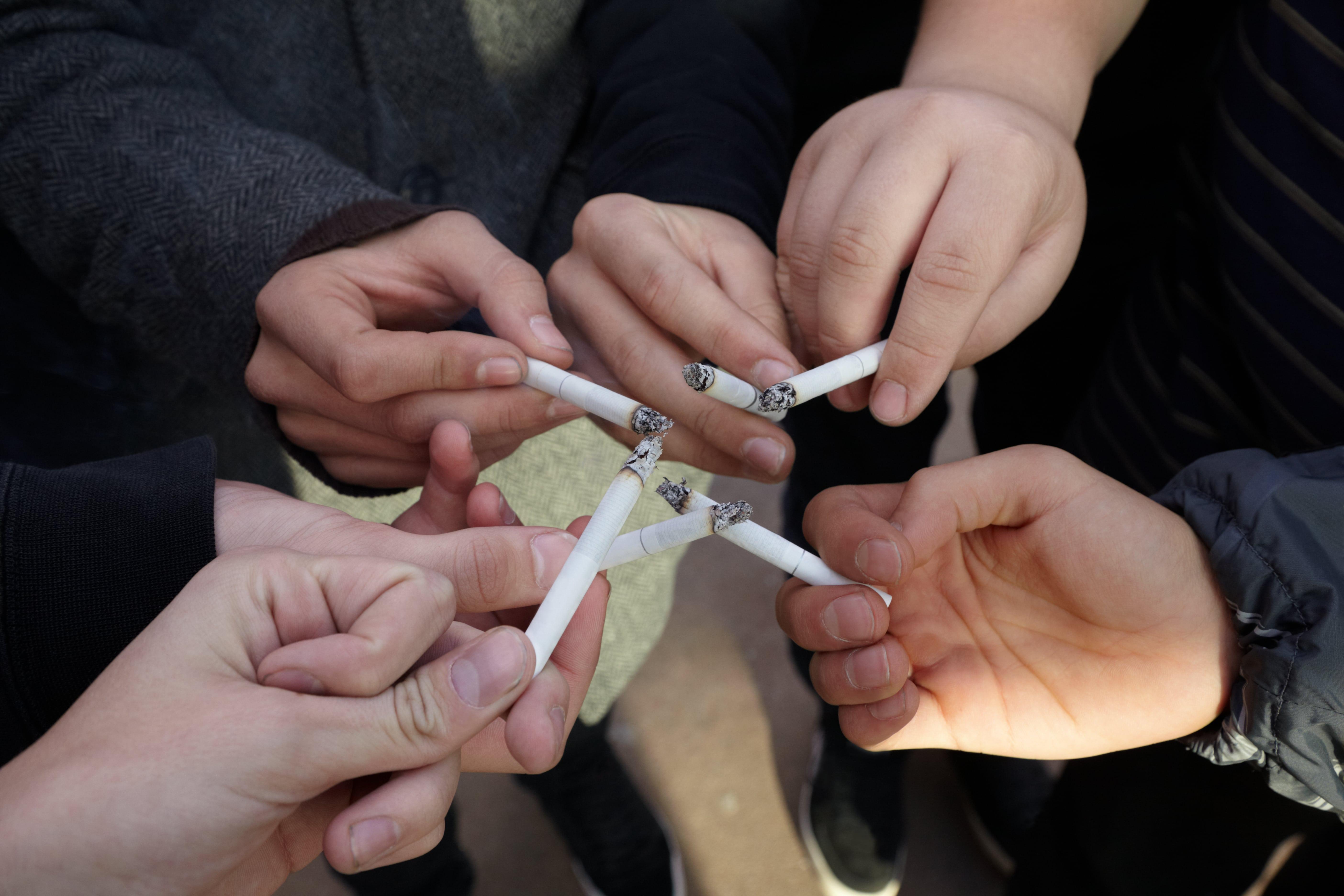 Wiele osób sięga po papierosa, aby dopasować się do osób zotoczenia.